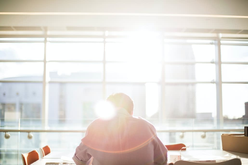 Somebody working at a desk in front of a sunlit window.